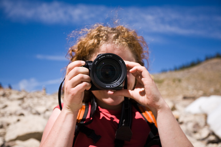 Young woman taking pictures with a DSLR camera