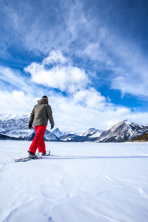 Young woman snowshoeing on a frozen lake in the Canadian Rocky Mountains, Kananaskis, Alberta, Canada