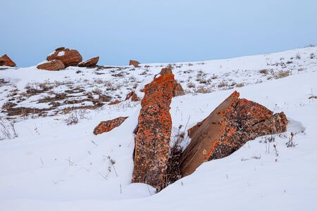 Large red boulders at Red Rock Coulee, Alberta, Canada in the evening on a cold winter day