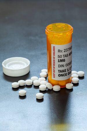 Prescription drug bottle with backlit generic tablets or pills.