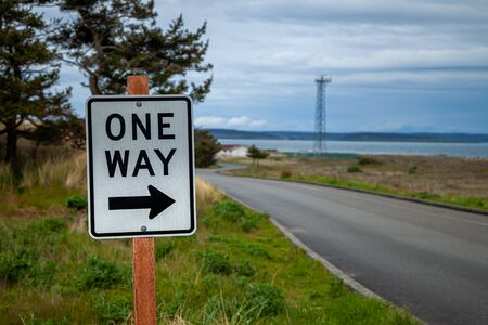 A One way road sign on a road in a park in Washington state, USA Foto de archivo - 129125079