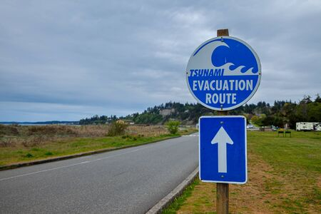 A sign showing a Tsunami Evacuation Route near the Pacific Ocean in Washington, USA Stock Photo - 129125081