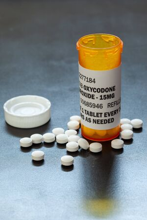 Prescription bottle with backlit Oxycodone tablets. Oxycodone is a generic prescription opioid. A concept of the opioid epidemic crisis 스톡 콘텐츠