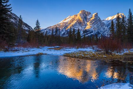 Mount Kidd, a mountain in Kananaskis in the Canadian Rocky Mountains, Alberta, Canada and the Kananaskis River in winter
