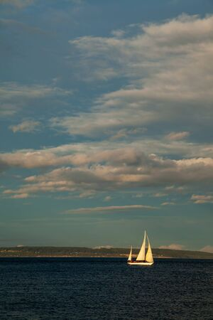 A small Sailboat on the water at sunset near Port Townsend, Washington, USA Stock Photo