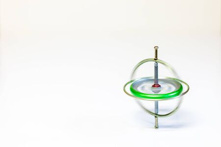 A spinning metal toy gyroscope isolated on a white background