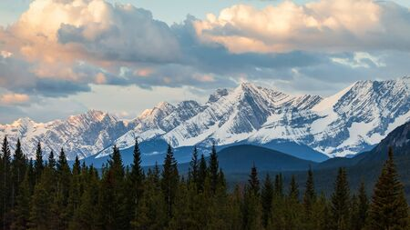 A moody sky at sunrise over a mountain range in Kananaskis Country, Alberta, Canada