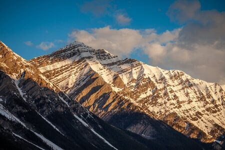 The early morning sun lighting up a mountain in Kananaskis Country, Alberta, Canada