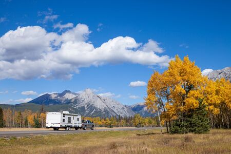An RV aon the highway through the Canadian Rocky Mountains in Kananaskis, Alberta, Canada during the peak of autumn colors Stockfoto