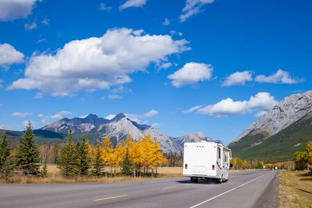 An RV aon the highway through the Canadian Rocky Mountains in Kananaskis, Alberta, Canada during the peak of autumn colors Stock Photo
