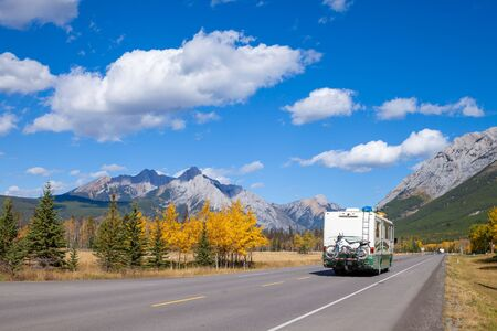 An RV aon the highway through the Canadian Rocky Mountains in Kananaskis, Alberta, Canada during the peak of autumn colors Archivio Fotografico