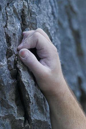 A single male hand on a cliff, rock climbing Banco de Imagens