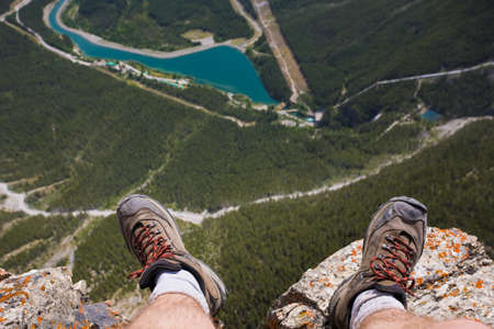 Close up of hikers feet and shoes dangling over a cliff near Canmore Alberta