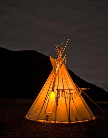 An iluminated Native American Teepee at night