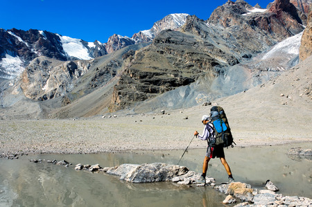 trekking pole: Man with big backpack resting on trekking pole moves a mountain river Stock Photo