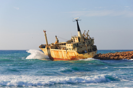 large rusty ship on the shore during a storm Stock Photo