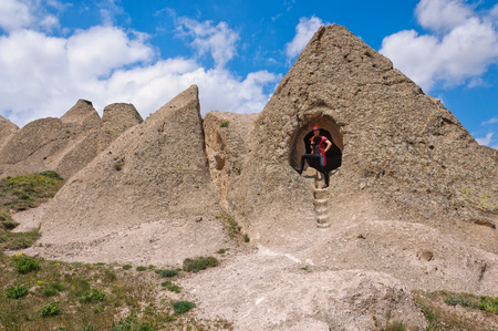 pidgeon: young man stands at the entrance to a cave in the cave city, Cappadocia, Turkey Stock Photo