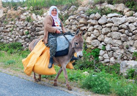 donkey: An elderly woman carries yellow bags on a donkey. Tajikistan trekking