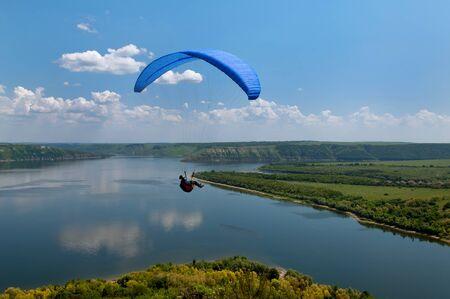 high flier: Paraglider above Bakota beautiful reservoir in the clouds. Ukraine