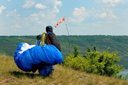 high flier: Paraglider prepares to fly over beautiful Bakota reservoir. Ukraine