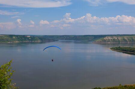 paraglider: Paraglider above Bakota beautiful reservoir in the clouds. Ukraine