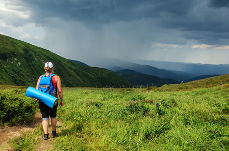 downwards: Young woman with a large backpack stands on hill and looks downwards in a thunderstorm
