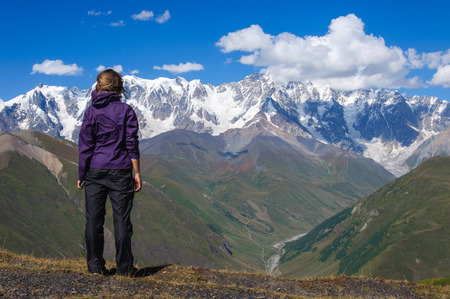 admires: Young woman admires the snow-capped mountains in Georgia Stock Photo