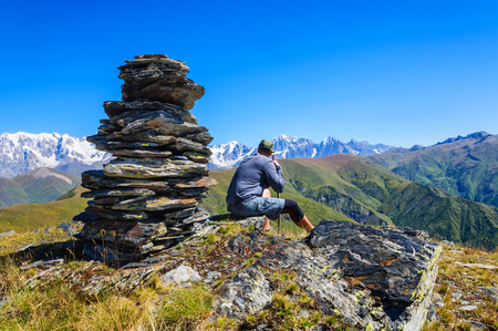 admires: Young man admires the snow-capped mountains in Georgia Stock Photo