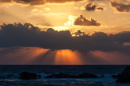 breaking through: sunset at the Mediterranean sea. slanting rays breaking through the clouds