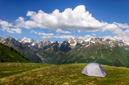 caucas: The gray tent in high grass on a background of mountains and rocks. Georgia. Stock Photo
