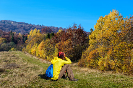 village man: young man looking at a country road and yellow autumn forest. Ukraine, the Carpathian mountains
