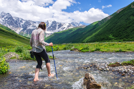 young girl crossing mountain river barefoot