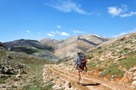 backpacker with backpack walking on dirt road in Mountains, southern Turkey