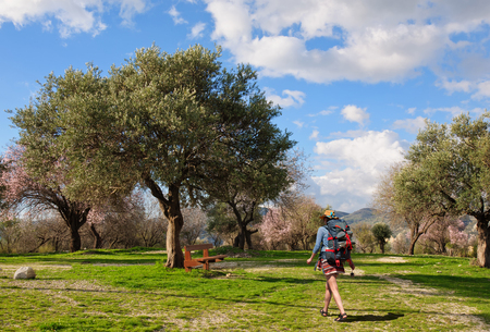 A young girl with a big backpack goes to rest on a bench under the old olive tree