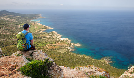 man with backpack sitting on a rock and looking at the Mediterranean Sea Imagens