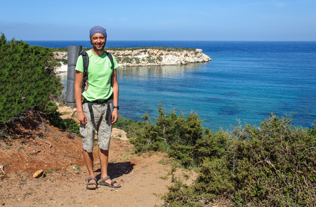 man with a backpack stands on the shore of the Mediterranean Sea and looks into the distance