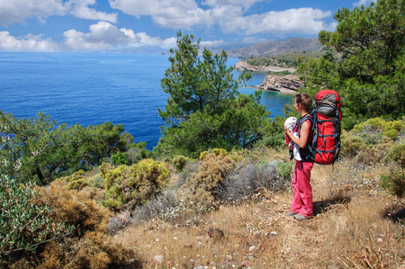 A woman with a baby in a sling and a large backpack travels along the Carian path. Turkey Stock Photo