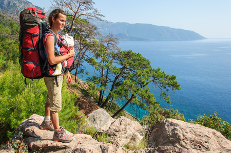 Mom with baby in a sling and a large backpack stands on top of the sea landscape. Turkey. Lycian Way