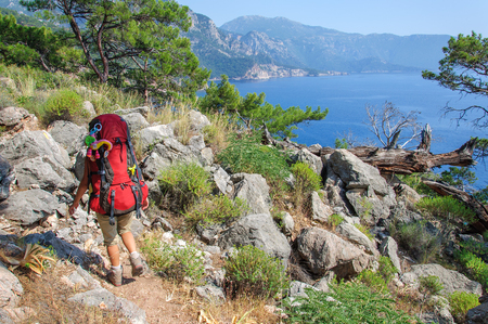 girl with a large backpack walks along the Lycian trail against the background of the sea and pines. Turkey Stockfoto