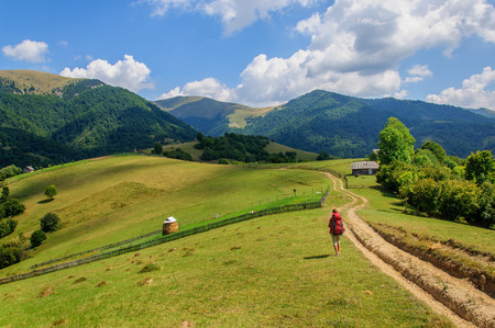 girl with a big backpack rises to the mountains. Ukraine
