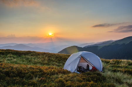 a gray tent on a grassy slope against the backdrop of a mountain range sunset in the Carpathians Ukraine