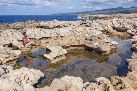 mother with baby in sling sitting on rock and looking at the Mediterranean Sea