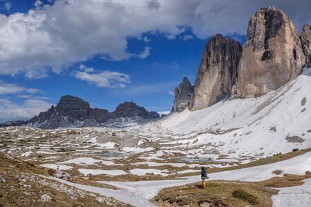 Young woman with backpack walks along dolomites, Italy. Banco de Imagens