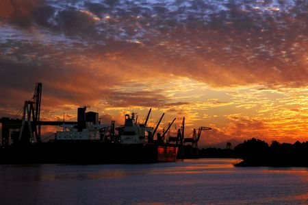seaport: Red Cargo Ship and Dramatic Sunset near Seaport Loading Docks Stock Photo