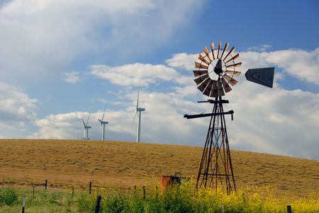 Old Ranch Windmill Contrasted Against New Electrical Power Generating Windmills, Digital Velvia, Rio Vista, California Stock Photo