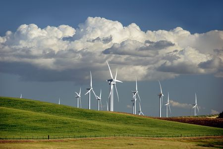 Stark White Electrical Power Generating Windmills on Rolling Hills, Beneath Dramatic Spring Cumulous Clouds, Rio Vista, California photo
