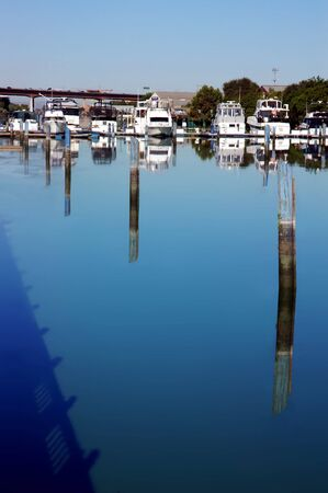 Pleasure Boats and Cityscape Reflected in Still River, Stocton California
