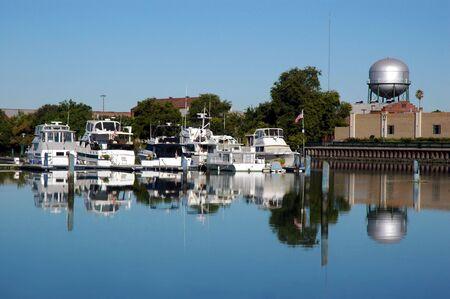 california delta: Pleasure Boats, Silver Water Tower, and Cityscape Reflected in Still River, Stocton California