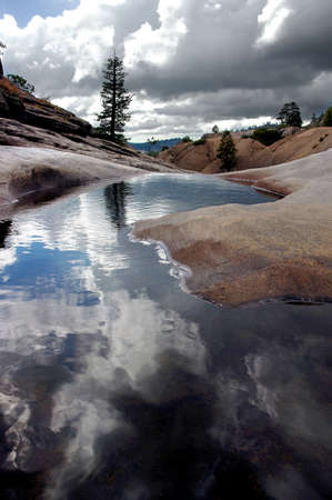 sierra: Lone Pine Tree, Red Glacial Granite, and Storm Clouds Reflected in a Quiet Pool, Cleos Bath, Sierra Nevada Range, Stanislaus National Forest, California
