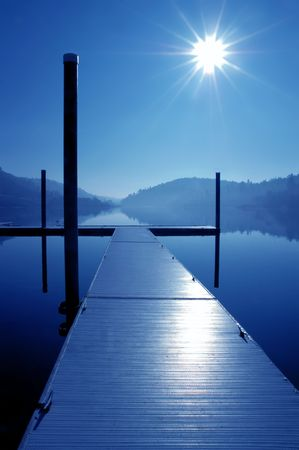 Dock, Blazing Sun, and Mirror Lake Reflection, in Blue Mood Stock Photo